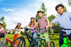 Row of happy children in bike colorful helmets Stock Images
