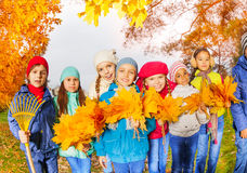 Row of happy kids with rake and leaves bunches Stock Image