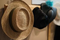Row of hats on display. Closeup of straw hat and retro hats all hanging on pegs in a hall Stock Photo
