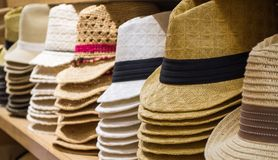 Row of hats on shelves. Row of colorful sunhats and Panama hats on shelves in a shop Royalty Free Stock Photo