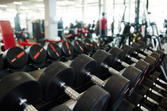 Row of Heavy Dumbbells in Gym. Background image: row of dumbbells on rack in empty modern gym stock photos