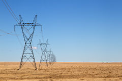 Row High Voltage Power Lines under a Blue Sky Royalty Free Stock Images