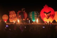 A row of hot air balloons lit up at night stock photo
