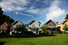 Row of Houses. Row of Multi-Colored Houses with Blue Sky and Green Grass Royalty Free Stock Image