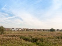 Row of houses on coast edge behind field across the way sky and Stock Photo