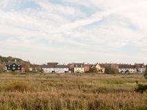 Row of houses on coast edge behind field across the way sky and Stock Photography
