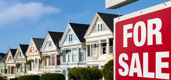 Row houses for sale in San Francisco. Dreaming of buying one of those colorful iconic San Francisco row houses. For Sale sign is visible in front royalty free stock photography