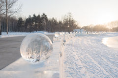 Row of ice balls at sunset in winter Stock Photos