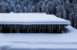Row of icicicles hanging from snow covered chalet rooftop Stock Photo