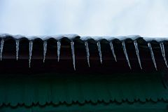 Row of icicles on the roof of the house against the green wall Stock Photo