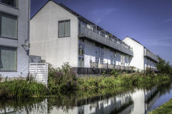 Residential houses next to river. A row of almost identical residential houses next to a river Royalty Free Stock Photo