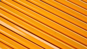 Row of identical sharpened pencils with orange coating. Equality concept, dolly. Clip stock video footage