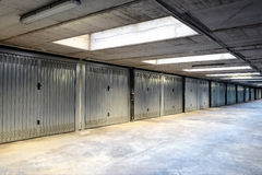Row of internal garages or lock-ups. With metal doors inside a commercial building with overhead lighting stock photography