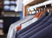 Row of jackets on hangers in men clothing store. Row of luxury jackets on hangers in men clothing store Royalty Free Stock Photo