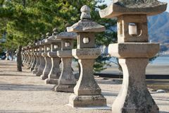 Row of Japanese stone lanterns. Miyajima, Japan, leading to Kiyomori shrine Stock Image