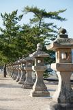 Row of Japanese stone lanterns. Miyajima, Japan, leading to Kiyomori shrine Stock Photos