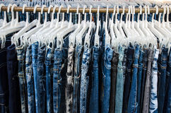 Row of Jeans and trousers on hangers for sale Stock Images