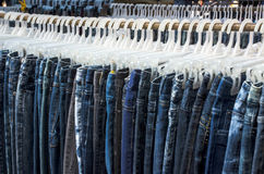 Row of Jeans and trousers on hangers for sale Stock Photo