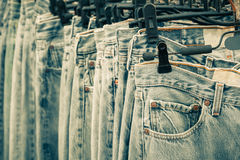 Row of Jeans and trousers on hangers. Stock Image