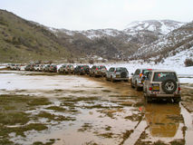 Row of jeeps in mountain. A row of jeeps driving in snow and mud in mountain terrain stock photography