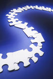 Row of Jigsaw Puzzle Pieces. On Blue Background Stock Photo