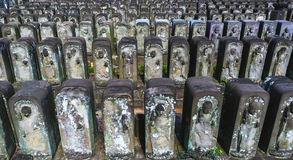 Row of jizo statues. Tokyo, Japan - April 06, 2015: Rows of Jizo statues in a state of disrepair at Jomyo-in temple in Tokyo.  The temple is famous for having Royalty Free Stock Photos