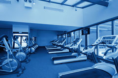 Row of jogging simulators in gym, monochromatic Stock Image