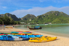 Row of Kayaks canoes boats on the PhiPhi Don beach in Thailand Royalty Free Stock Image