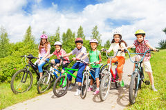 Row of kids diversity in helmets and bikes Stock Photos