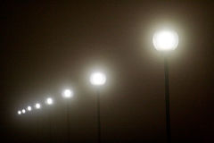 Row of lamp posts glowing in the dark Royalty Free Stock Images