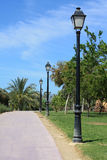 Row of lampposts in park. Line of lampposts along a park lane in a tropical garden Royalty Free Stock Images