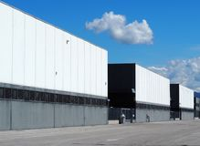 A row of large black and white industrial warehouse buildings with the road in front . Fluffy clouds in the sky royalty free stock photography
