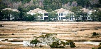 A row of large houses across a salt-marsh. stock image