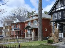 Row of large old  detached brick houses. With mature trees in the front yard royalty free stock photography