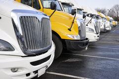Row of large trucks. View of the front end of large trucks in a row Royalty Free Stock Images
