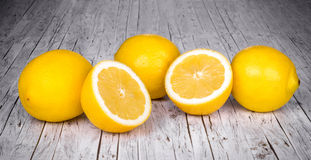 A row of lemons on a wood table. A row of lemons on a wood kitchen table Royalty Free Stock Photos