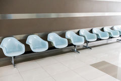 Row of light blue chairs in the hospital hallway Stock Images