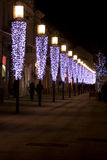 Row of light posts. People walking along a row of lights Royalty Free Stock Images
