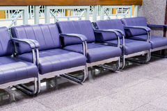 Row of light purple chairs in the hospital hallway. Light purple chairs alignment in a waiting area Royalty Free Stock Images