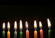 Row of lit candles. Row of several lit candles over black background Stock Photography