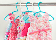 Row of little girl dresses hanging on coat hanger in white wardr Royalty Free Stock Image