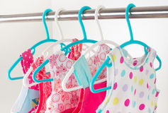 Row of little girl dresses hanging on coat hanger in white wardr Royalty Free Stock Photography