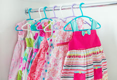 Row of little girl dresses hanging on coat hanger in white wardr Royalty Free Stock Images