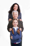 Row of little girl, grandmother, mother looking at camera in lin Stock Photos
