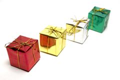 Row of little presents. Four little gift boxes in a row isolated Stock Photography