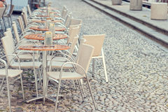 Row of little tables with chairs  in open cafe. A row of small tables of a cafe on a pedestrian street Royalty Free Stock Photography