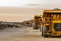 A row of lLarge Mining Dump Trucks for transporting ore rocks. A row of large yellow Dump Trucks transporting Platinum ore for processing at sunset Stock Photography