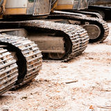 Row of loaders and tracks. Row of yellow and white construction loaders and tracks Royalty Free Stock Photos