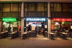 Row of local steakhouse and restaurants in red-light district in Amsterdam, the Netherlands. Amsterdam-May 01: Row of local steakhouse and restaurants in red royalty free stock photos