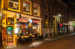 Row of local steakhouses and restaurants at night in red-light district in Amsterdam, the Netherlands. Stock Photos